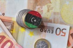 Euro moneta con la bandiera nazionale della Libia sugli euro precedenti delle banconote dei soldi Immagini Stock
