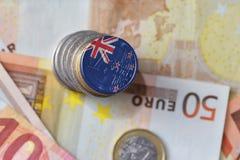 Euro moneta con la bandiera nazionale della Nuova Zelanda sugli euro precedenti delle banconote dei soldi Fotografie Stock Libere da Diritti