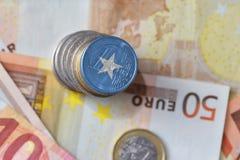 Euro moneta con la bandiera nazionale della Somalia sugli euro precedenti delle banconote dei soldi Fotografia Stock