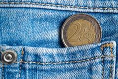Euro moneta con una denominazione dell'euro 2 nella tasca dei jeans blu scuro del denim fotografie stock libere da diritti