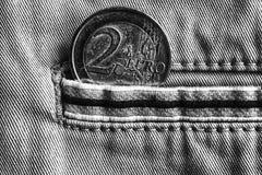 Euro moneta con una denominazione dell'euro 2 nella tasca dei jeans del denim con la banda, colpo monocromatico Fotografia Stock