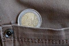 Euro moneta con una denominazione dell'euro 2 nella tasca dei jeans grigi d'annata del denim fotografie stock libere da diritti