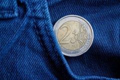Euro moneta con una denominazione dell'euro 2 nella tasca di vecchi jeans blu d'annata del denim immagine stock