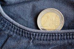 Euro moneta con una denominazione dell'euro 2 nella tasca di vecchi jeans blu del denim fotografia stock libera da diritti