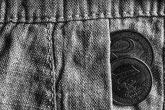 Euro moneta con una denominazione dell'euro uno e due nella tasca dei pantaloni di tela consumati, colpo monocromatico Immagine Stock Libera da Diritti
