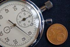 Euro moneta con una denominazione di 5 euro centesimi e cronometri sul contesto nero del denim - fondo di affari fotografia stock libera da diritti