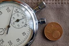 Euro moneta con una denominazione di 2 euro centesimi e cronometri sul vecchio contesto beige dei jeans - fondo di affari fotografie stock