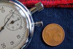 Euro moneta con una denominazione di 5 euro centesimi e cronometri sulle blue jeans consumate con il contesto rosso della banda - fotografia stock