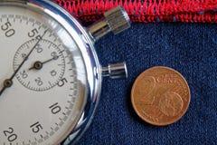 Euro moneta con una denominazione di 2 euro centesimi e cronometri sulle blue jeans consumate con il contesto rosso della banda - fotografia stock