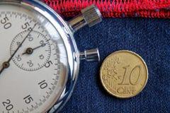 Euro moneta con una denominazione di 10 euro centesimi e cronometri sulle blue jeans consumate con il contesto rosso della banda  Fotografia Stock