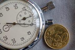 Euro moneta con una denominazione di 50 euro centesimi e del cronometro sul contesto grigio del denim - fondo di affari Fotografia Stock