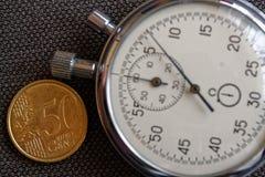 Euro moneta con una denominazione di 50 euro centesimi e del cronometro sul contesto marrone del denim - fondo di affari Immagini Stock Libere da Diritti