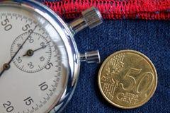 Euro moneta con una denominazione di 50 euro centesimi e del cronometro sulle blue jeans consumate con il contesto rosso della ba Immagine Stock