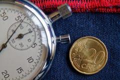 Euro moneta con una denominazione di 20 euro centesimi e del cronometro sulle blue jeans consumate con il contesto rosso della ba Fotografie Stock