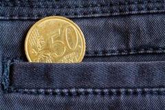Euro moneta con una denominazione di 50 euro centesimi nella tasca dei jeans blu scuro del denim Immagine Stock