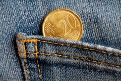 Euro moneta con una denominazione di 20 euro centesimi nella tasca dei jeans portati blu del denim Immagine Stock