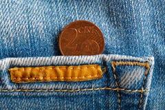 Euro moneta con una denominazione di euro centesimo due nella tasca della cucitura arancio del denim di whis blu consumati dei je immagini stock