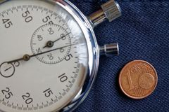Euro moneta con una denominazione di 1 euro centesimo e cronometro sul contesto blu obsoleto del denim - fondo di affari Fotografia Stock
