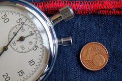 Euro moneta con una denominazione di 1 euro centesimo e cronometro sulle blue jeans consumate con il contesto rosso della banda - Fotografia Stock