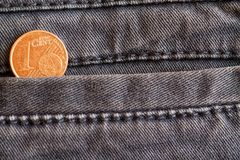 Euro moneta con una denominazione di 1 euro centesimo nella tasca dei jeans blu consumati del denim fotografia stock