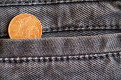 Euro moneta con una denominazione di euro centesimo 2 nella tasca dei jeans blu consumati del denim fotografia stock