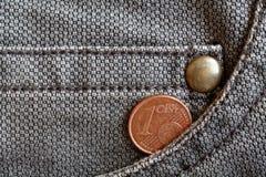 Euro moneta con una denominazione di 1 euro centesimo nella tasca dei jeans marroni consumati del denim Immagine Stock Libera da Diritti