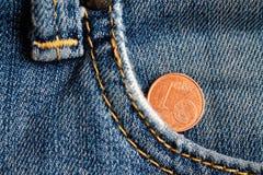 Euro moneta con una denominazione di 1 euro centesimo nella tasca di vecchi jeans blu portati del denim fotografia stock libera da diritti