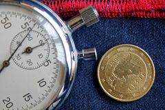 Euro moneta con una denominazione di cinquanta euro centesimi (lato posteriore) e del cronometro su denim blu consumato con il co Immagini Stock Libere da Diritti