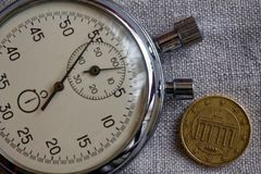 Euro moneta con una denominazione di dieci euro centesimi e cronometri sul contesto di tela bianco - fondo di affari Immagini Stock Libere da Diritti