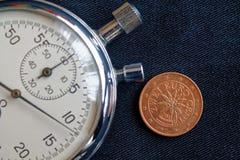 Euro moneta con una denominazione di due euro centesimi (lato posteriore) e del cronometro sul contesto nero consumato del denim  fotografie stock libere da diritti