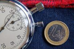 Euro moneta con una denominazione di 1 euro e cronometro sulle blue jeans consumate con il contesto rosso della banda - fondo di  immagine stock