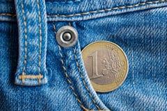 Euro moneta con una denominazione di 1 euro nella tasca dei jeans blu-chiaro del denim immagine stock libera da diritti