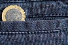 Euro moneta con una denominazione di 1 euro nella tasca dei jeans blu consumati del denim fotografie stock
