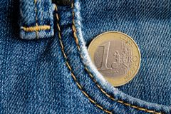Euro moneta con una denominazione di 1 euro nella tasca dei jeans blu del denim fotografia stock