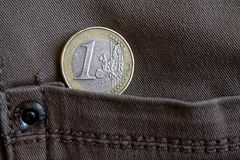 Euro moneta con una denominazione di 1 euro nella tasca dei jeans marroni del denim fotografia stock