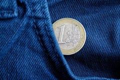 Euro moneta con una denominazione di 1 euro nella tasca di vecchi jeans blu consumati del denim immagini stock libere da diritti