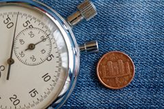 Euro moneta con una denominazione di un euro centesimo (lato posteriore) e del cronometro sul contesto blu consumato del denim -  Immagine Stock Libera da Diritti