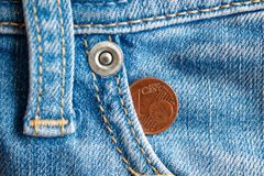Euro moneta con una denominazione di un euro centesimo nella tasca di vecchi jeans blu d'annata portati del denim fotografia stock
