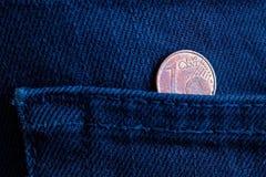 Euro moneta con una denominazione di un euro centesimo nella tasca di vecchi jeans blu scuro del denim immagini stock libere da diritti