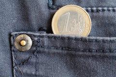 Euro moneta con una denominazione di un euro nella tasca dei jeans blu scuro del denim fotografia stock