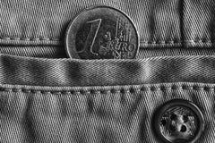 Euro moneta con una denominazione di un euro nella tasca dei jeans del denim con il bottone, colpo monocromatico Fotografia Stock Libera da Diritti