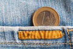 Euro moneta con una denominazione di un euro nella tasca di vecchi jeans blu consumati del denim con la cucitura arancio immagini stock libere da diritti