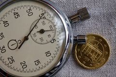 Euro moneta con una denominazione di venti euro centesimi (lato posteriore) e del cronometro sul contesto bianco del lino - fondo Immagine Stock Libera da Diritti