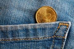 Euro moneta con una denominazione di venti euro centesimi nella tasca di vecchi jeans portati blu del denim immagini stock libere da diritti