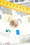 Euro moneta dei soldi sulle banconote vicino al nastro di misura Immagini Stock