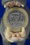 Euro moneta del Greco uno in bocca della figurina dell'ippopotamo Immagini Stock Libere da Diritti