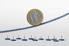 Euro moneta na arkanie nad pchnięcie szpilkami - pojęcie tendencja wzrostowa euro waluty i euro waluty ryzyko zdjęcie royalty free