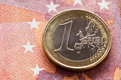 Euro moneta su una banconota da dieci euro Fotografie Stock