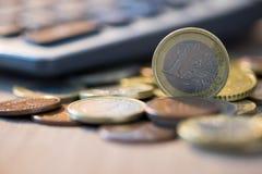Euro monete con il calcolatore, concetto dei soldi, fine sulle euro monete Fotografia Stock