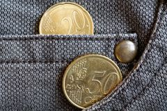 Euro monete con una denominazione di 20 e 50 euro centesimi nella tasca dei jeans marroni consumati del denim Fotografia Stock Libera da Diritti